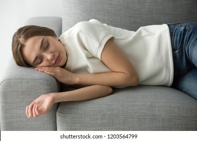 Attractive calm woman sleeping on comfortable soft couch in living room, beautiful girl falling asleep, resting, relaxing on sofa, having daytime sleep, laying with closed eyes, calmness and carefree