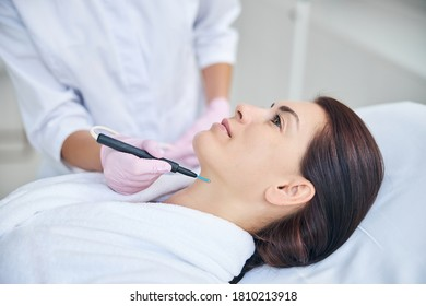 Attractive calm woman in a terry bathrobe lying still during the electrosurgical procedure in a beauty parlor