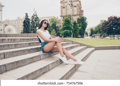 Attractive carefree gorgeous lady with bronze skin is posing in town, on stroll, sitting on concrete stone rung, in trendy eyewear, white top, in denim short shorts, so fit and slim body