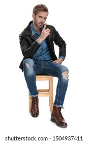 attractive casual man with black leather jacket is sitting on a wooden chair with one hand leaning on leg and pointing up serious on white background studio