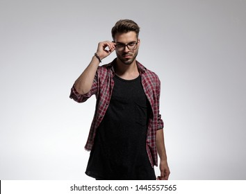 Attractive casual man fixing his glasses while wearing a black t-shirt and a checkered shirt, standing on gray studio background