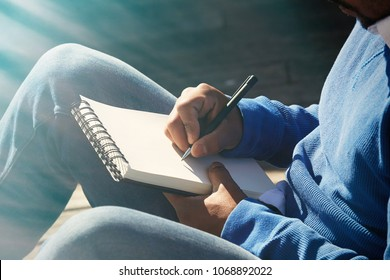 Attractive casually dressed young american african man making notes in copybook pad. Student preparing for lesson at college