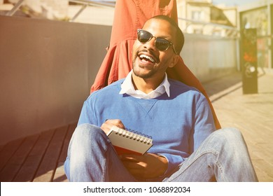 Attractive casually dressed young black male student with sunglasses making notes in copybook, preparing for lesson at college
