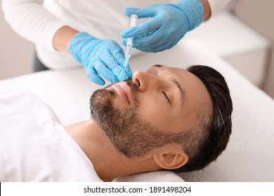 Attractive caucasian bearded man visiting aesthetic clinic, getting lips filler, closeup. Middle aged businessman having beauty injection at male spa. Face care, anti-aging treatment for men concept
