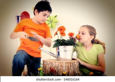 Attractive Caucasian boy and girl with flowers, tools, garden supplies.  Studio Portrait.