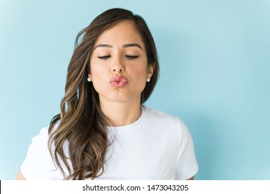 Attractive Caucasian brunette puckering lips isolated on blue background
