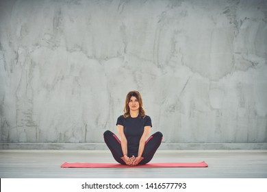 Attractive Caucasian brunette sitting on the mat barefoot in sukhasana.