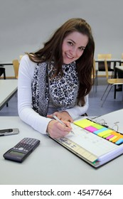 Attractive Caucasian Brunette studying with calculator and notepad, smiling into the camera