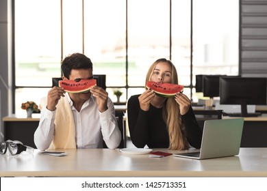 Attractive Caucasian business people eating watermelon in office. Summer vacations concept.
