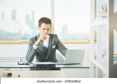 Attractive caucasian businessman drinking coffee and using laptop in modern office with blurry city view and items on desktop