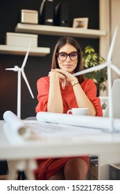 Attractive caucasian businesswoman in blouse and with eyeglasses posing in office. On deska are laptop, plan and windmill models. Sustainable development concept. - Shutterstock ID 1522178558