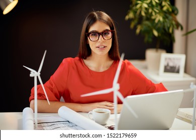 Attractive caucasian businesswoman in blouse and with eyeglasses posing in office. On deska are laptop, plan and windmill models. Sustainable development concept. - Shutterstock ID 1522179659