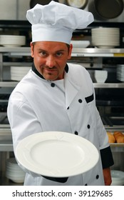 Attractive Caucasian chef holding an empty plate in a commercial kitchen