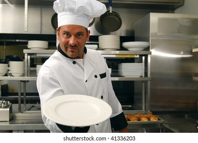 Attractive Caucasian chef holding an empty plate in a restaurant kitchen.
