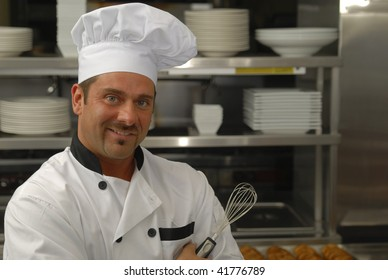 Attractive Caucasian chef holding a whisk in a restaurant kitchen.