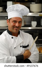 Attractive Caucasian chef holding a wooden spoon in a restaurant kitchen.