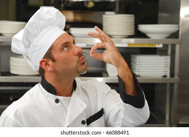 Attractive Caucasian chef kissing his fingers to show how tasty the food is.