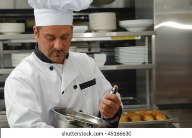 Attractive Caucasian chef mixing food in a bowl in a restaurant kitchen.