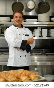 Attractive Caucasian chef standing with arms crossed in a restaurant kitchen.