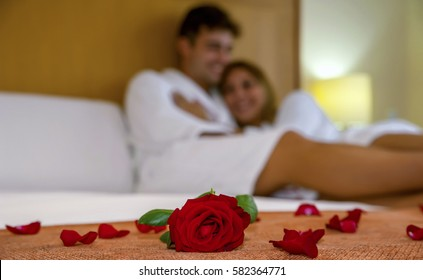 Attractive Caucasian couple in the background with rose and rose petals in the foreground. Blurred image of a romantic couple smiling with one rose and rose petals