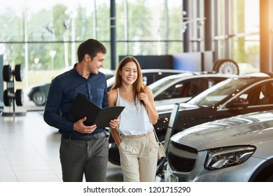 Attractive caucasian couple of fashionably dressed people standing at the dealership choosing the car to buy, man holds a black folder with documents