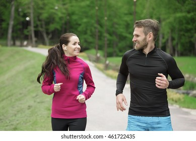 Attractive caucasian couple friends running in park.