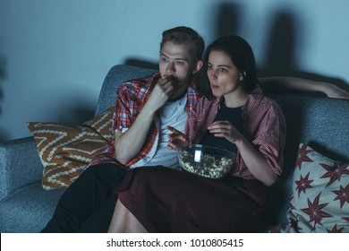 attractive caucasian couple watching thriller movie in dark room with popcorn on sofa fully attention
