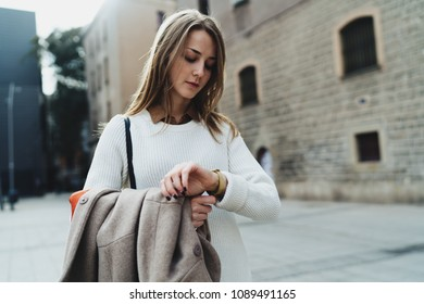 Attractive caucasian female looking at the watches while standing on a blurred urban background. Office worker checking the time while waiting for the colleague to go to the lunch together.