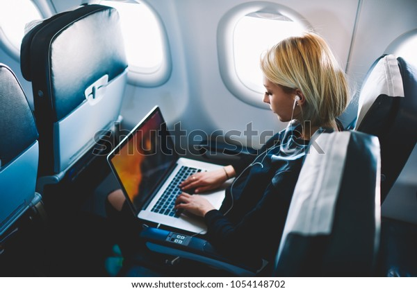 Attractive caucasian female passenger of airplane sitting in comfortable seat listening music in earphones while working at modern laptop computer with mock up area using wireless connection on board