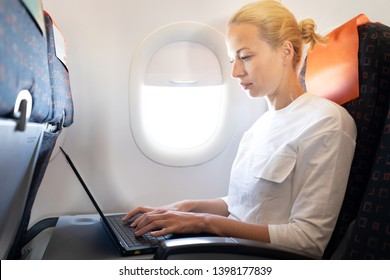 Attractive caucasian female passenger working at modern laptop computer using wireless connection on board of commercial airplane flight.