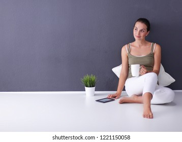 Attractive caucasian girl sitting on floor with cup and tablet near wall