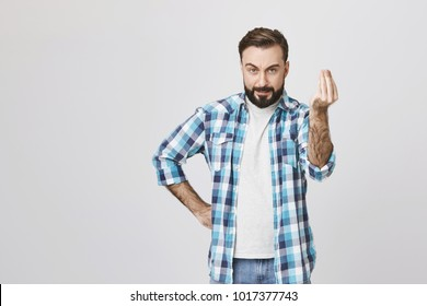 Attractive caucasian guy looking mad and angry, holding hand on waist while showing get to the point gesture with another, over gray background. Furious landlord says time is up and want his money