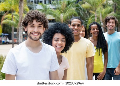 Attractive caucasian hipster man with beard with multi ethnic friends in line outdoor in the summer