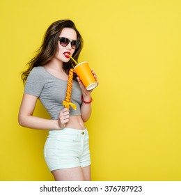 Attractive Caucasian joyful woman with a paper cup of juice and candy. Beautiful woman in sunglasses on a yellow background. Studio shot. Red lips.