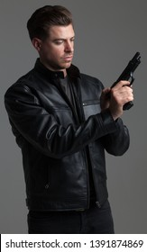 Attractive Caucasian Male with Brown Hair – Action Hero wearing Leather Jacket and Jeans, holding gun