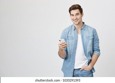 Attractive caucasian male brunette holding smartphone with one hand in pocket, smiling at camera, isolated over white background. Man was asked to find song that played at store minute ago