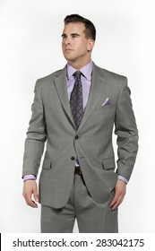Attractive caucasian male fitness model wearing a trendy fitted and fashionable gray suit with a purple shirt and tie underneath posing in a studio on a white background while looking to the left.