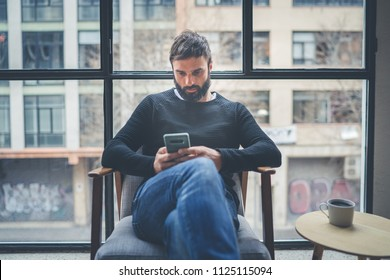 Attractive caucasian man in black pullover using mobile phone application for mobile blogging. Confident bearded young hipster guy read news from social network at modern loft.Blurred background