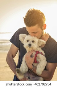 Attractive caucasian man is kissing his dog at the beach - concept about animals, people and lifestyle