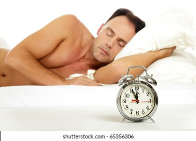 Attractive caucasian middle aged man sleeping and a retro alarm clock showing midnight. Focus on clock. Studio shot. White background.