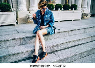 Attractive caucasian model dressed in stylish denim clothing posing for camera during photo session outside.Fashionable hipster girl in sunglasses spending free time sitting on ground at street