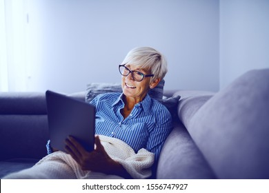 Attractive caucasian smiling blonde senior woman sitting on sofa in living room, using tablet and enjoying sunday afternoon.