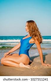 Attractive Caucasian woman in bikini relaxing at tropical beach in Bali.