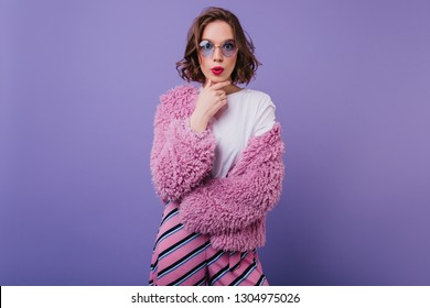 Attractive caucasian woman in bright attire looking to camera with surprised face expression. Indoor portrait of refined curly female model in pink fur coat.