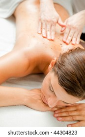 An attractive caucasian woman getting a scrub in a spa