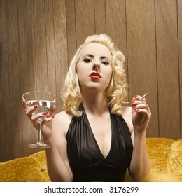 Attractive Caucasian woman holding a martini and cigarette.