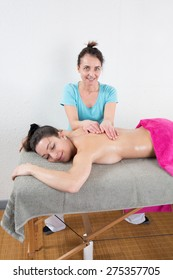 An attractive caucasian woman lying down on a massage table