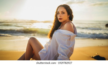 An attractive Caucasian woman posing on the beach during the sunset