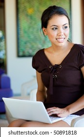 An attractive caucasian woman relaxing and using her laptop indoors