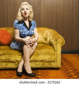Attractive Caucasian woman sitting on retro style couch.